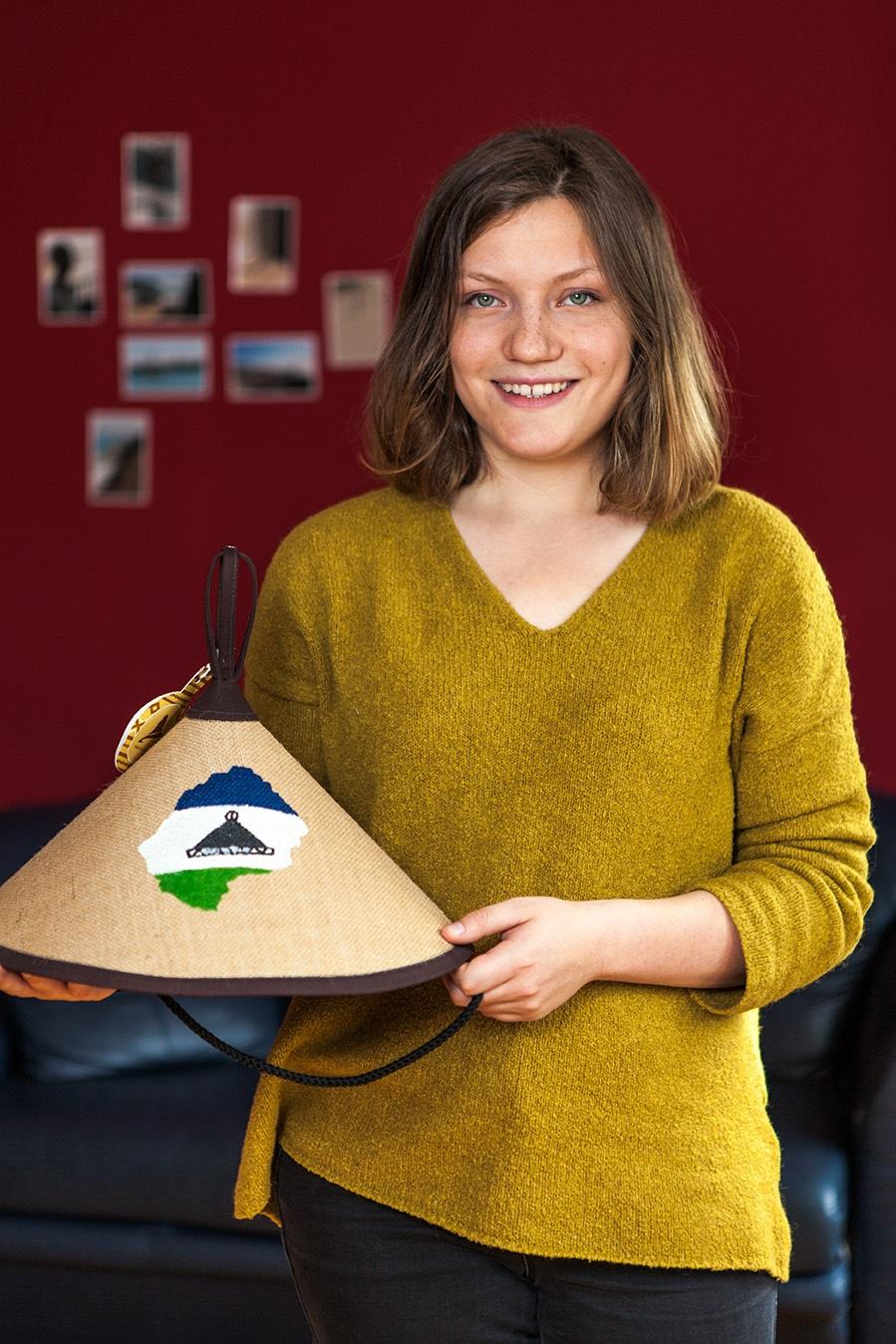 kulturweit-Alumna Eva Richter hält einen Hut in der Hand, den sie aus Lesothos Hauptstadt Maseru mitgebracht hat.