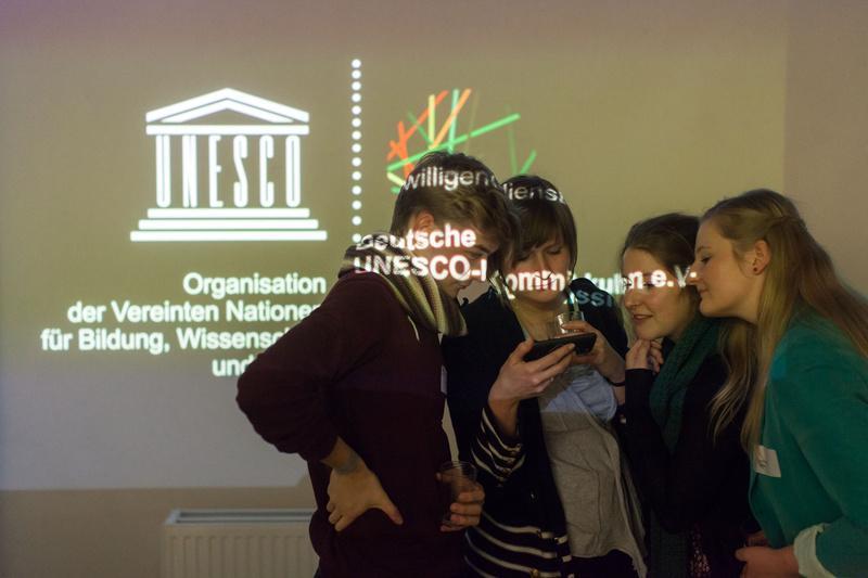 Junge Menschen vor kulturweit-Logo.