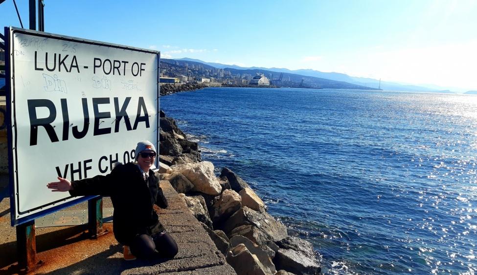 Sonja vor einem Schild am Wasser in Kroatien