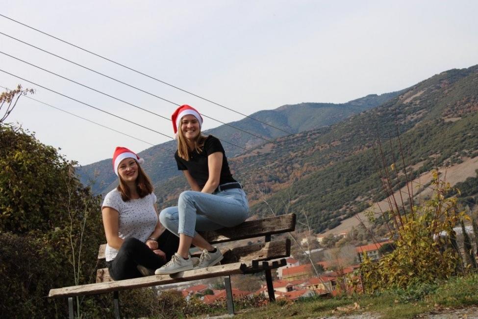 Lara und Maya sitzen auf einer Bank und tragen Weihnachtsmannmützen. Im Hintergrund sieht man ein Gebirge.