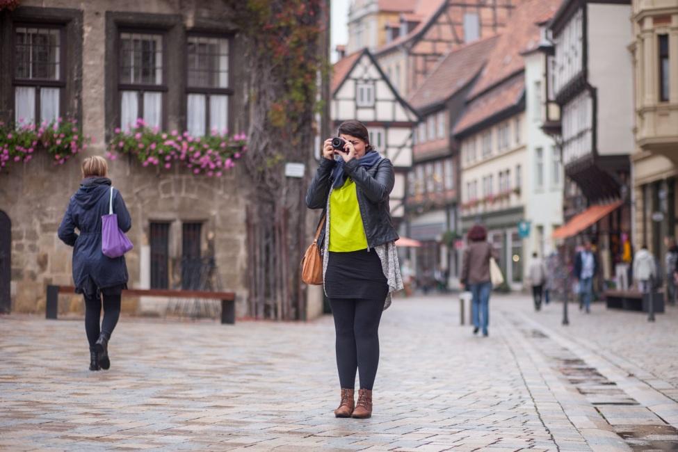 Junger Mensch steht auf einem Marktplatz und fokussiert ein Objekt mit seiner Kamera.