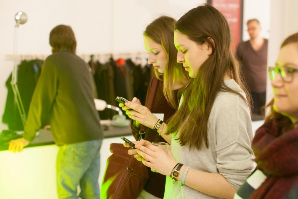 Zwei Freiwillige stehen an einer Garderobe und schauen in ihre Smartphones.