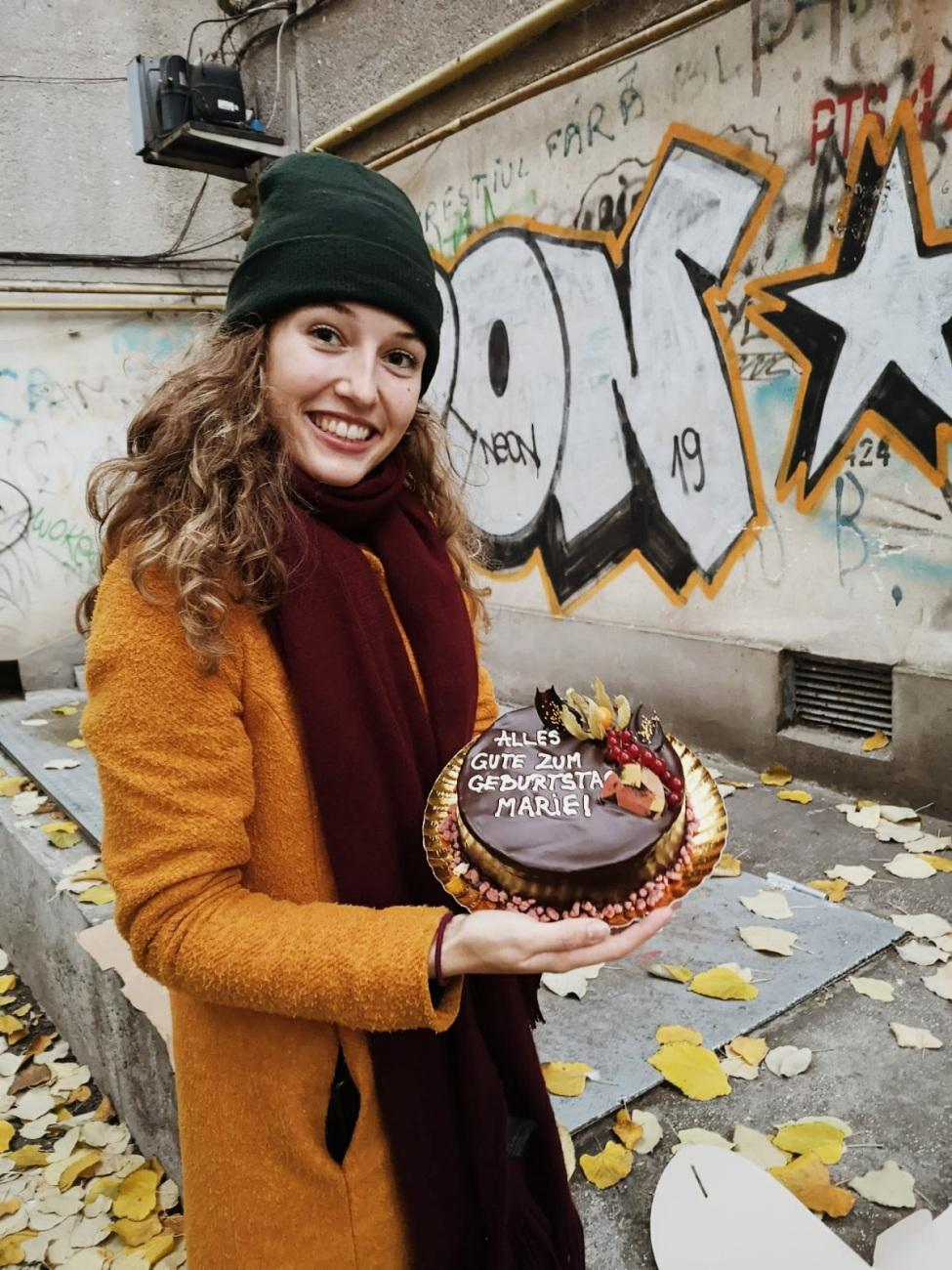 Marie mit einem Schokoladenkuchen in der Hand