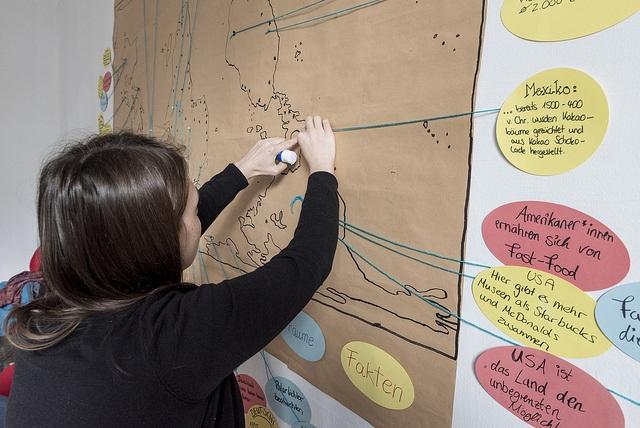 Junger Mensch verbindet eine Hinweiskarte mit einem Punkt auf einer Landkarte.