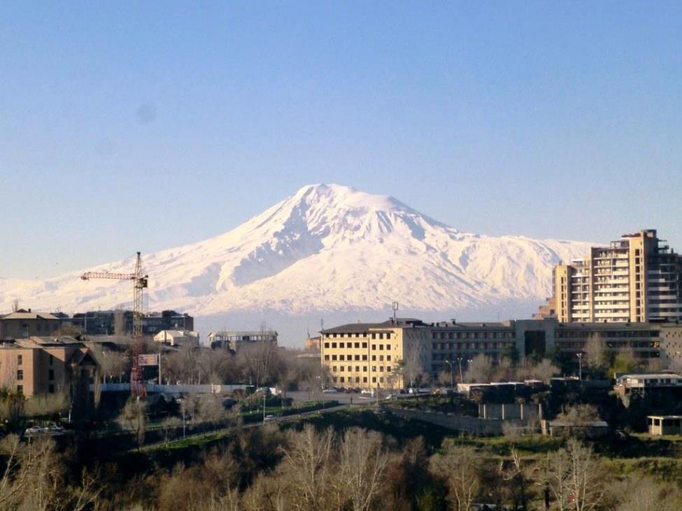 Blick auf einen Schneebedeckten Berg. Im Vordergrund Häuser der Stadt Jerewan