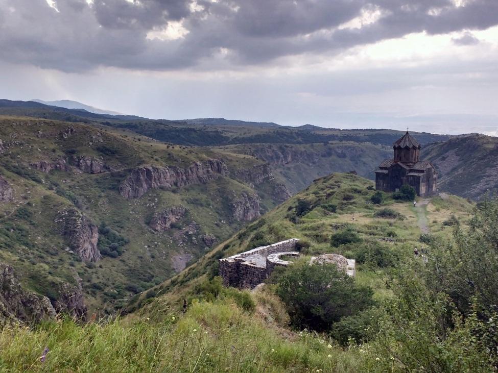 Blick auf die Burg Amberd in Armenien. Die Burg ist in der rechten Bildhälfte im Hintergrund und steht auf einem Berg.