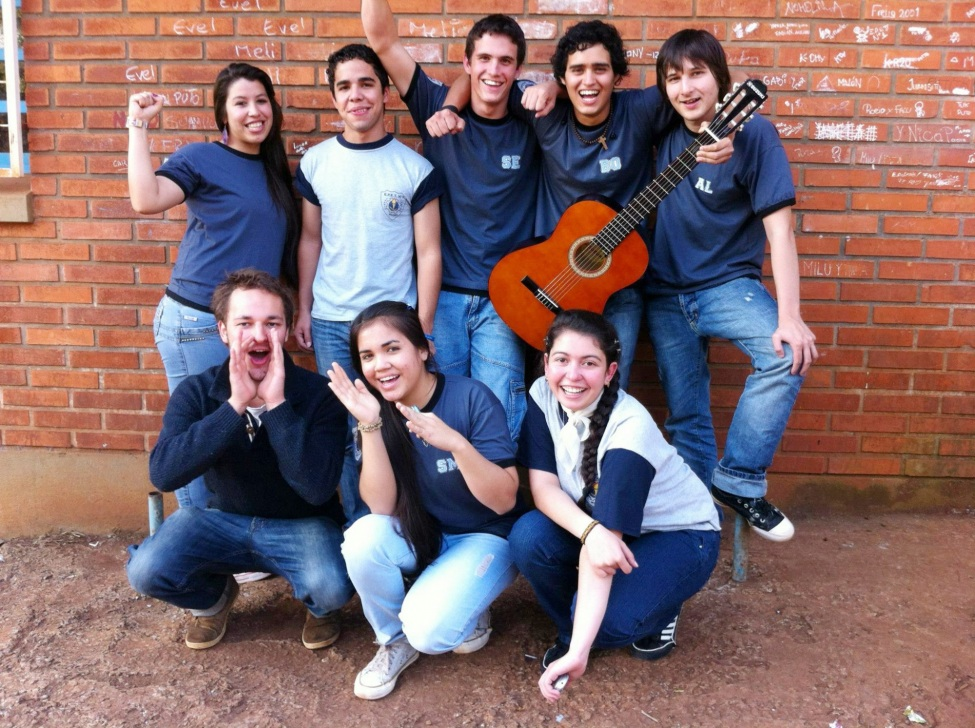 Jonathan und Schüler posieren vor einer roten Wand für ein Gruppenfoto