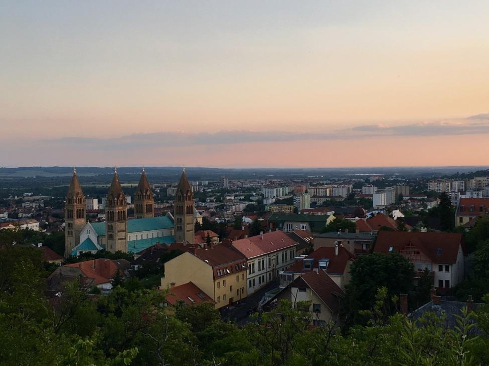 Blick auf Pécs in der Abenddämmerung, man sieht Kirchen, historische Gebäude und Wohnhäuser. im Vordergrund Bäume, im Hintergrund weite Landschaft und Felder