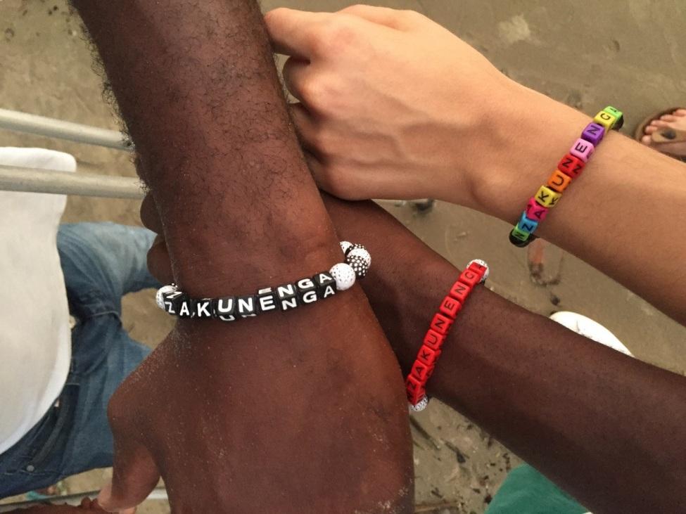 """die Armbänder, die sich viele Teilnehmer*innen haben machen lassen, mit dem Gruppennamen """"Nzakunenga"""""""