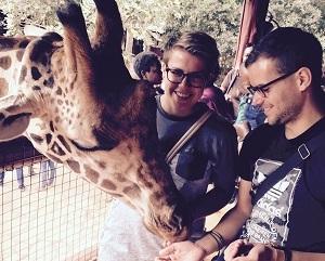 Freiwillige Christopher Rohles und Inken Koenemund füttern eine Giraffe