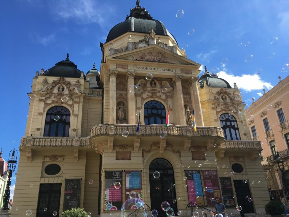 Vor einem historischen Gebäude fliegen Seifenblasen empor