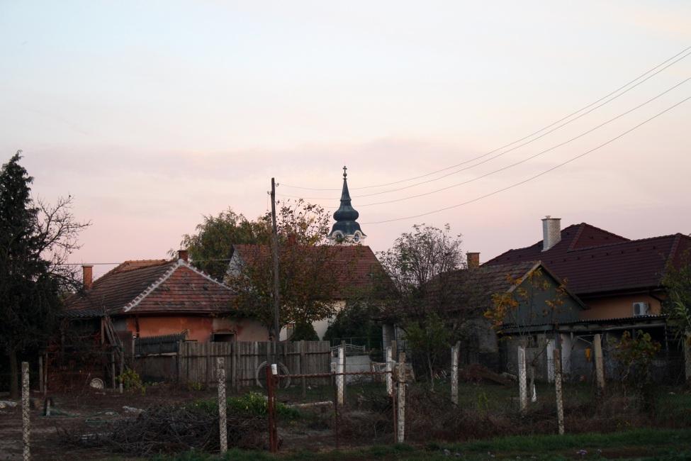 Blick auf kleine Steinäuser in Abendstimmung, im Hintergund ein Kirchturm