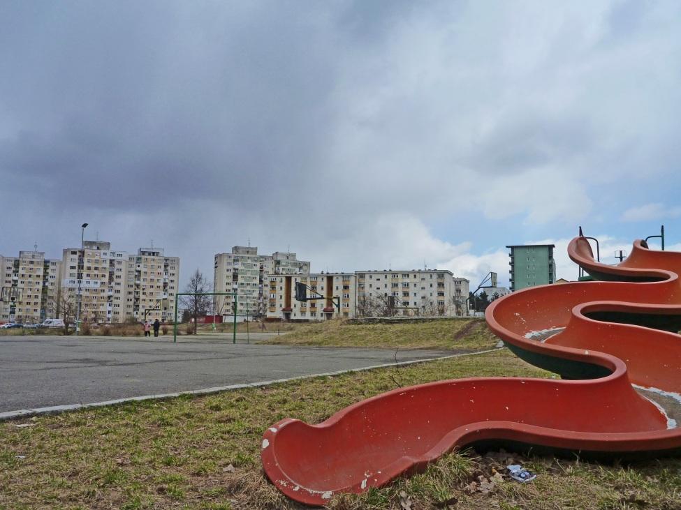 Rote Rutsche vor Häuserfassaden in Rumänien