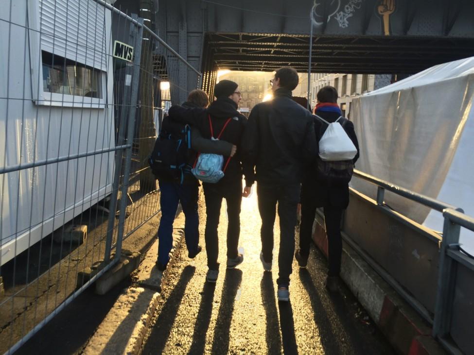 Vier Personene gehen in Berlin dem Sonnenuntergang entgegen.