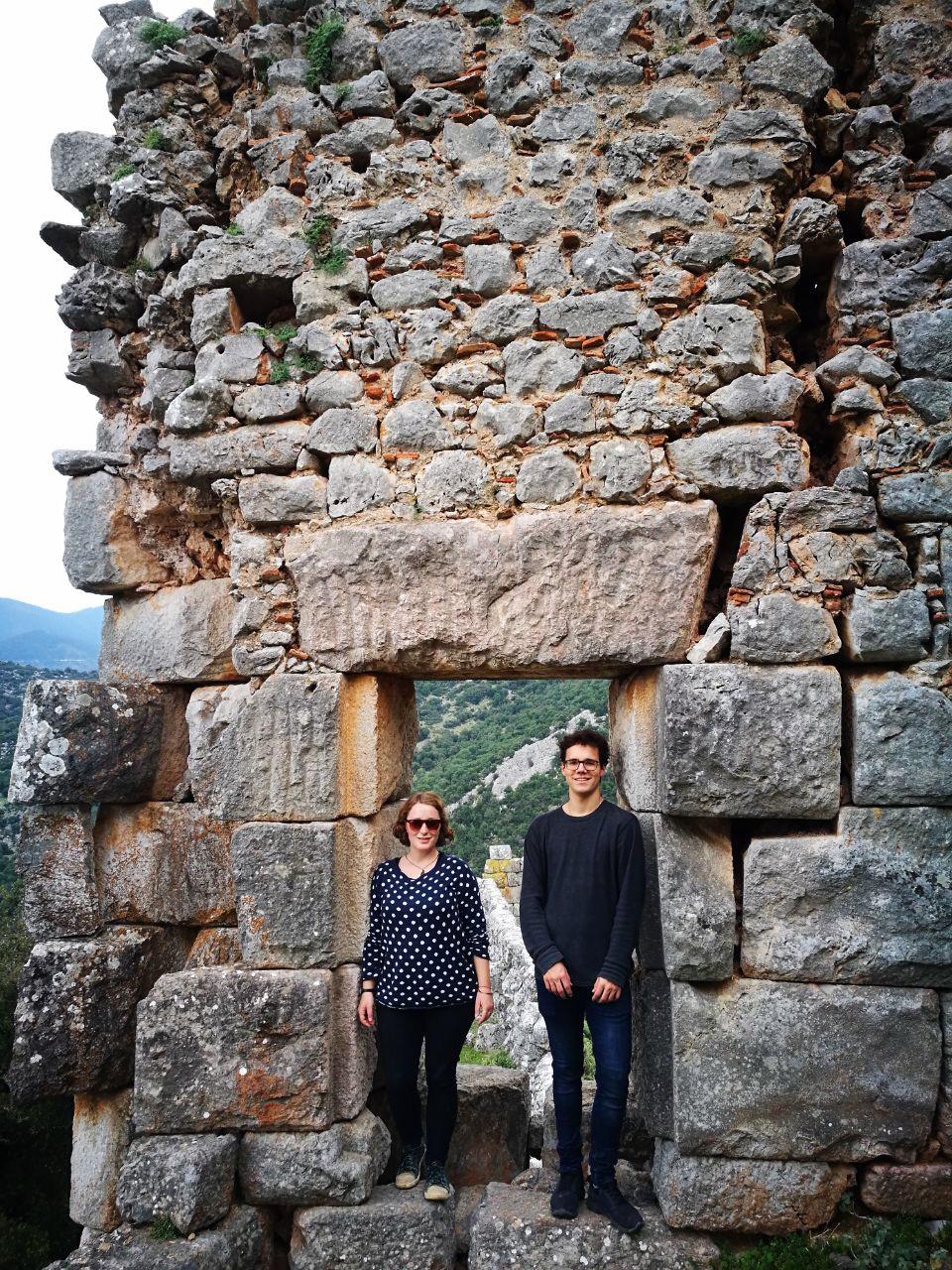 Maria und anderer Freiwilliger vor einer antiken griechischen Ruine aus Stein