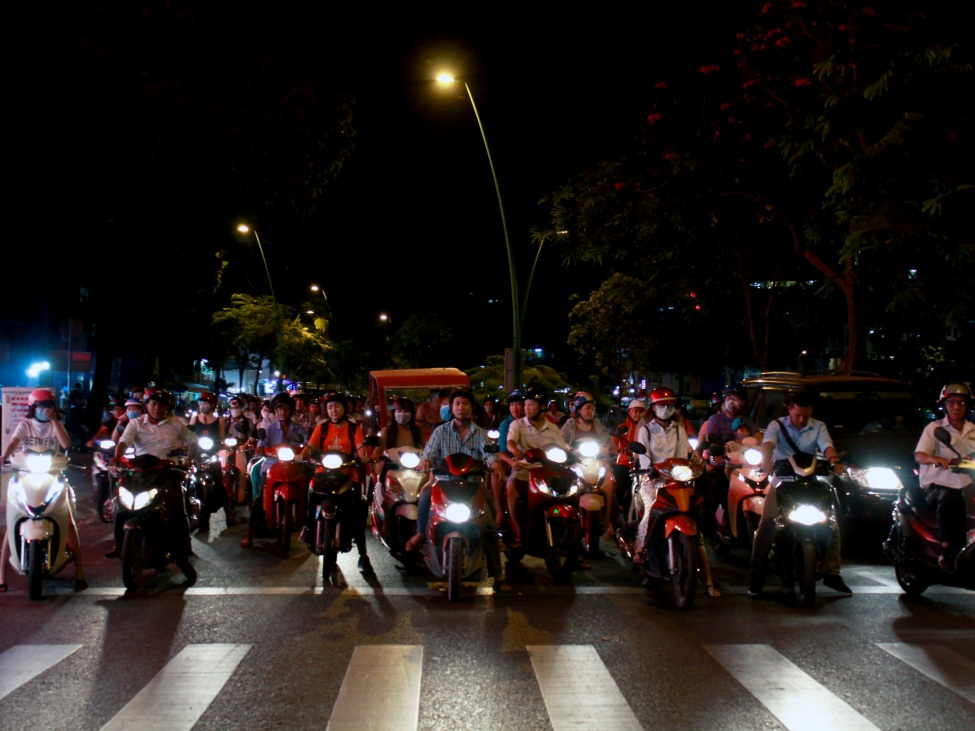 Mopedfahrer*innen in Saigon bei Nacht