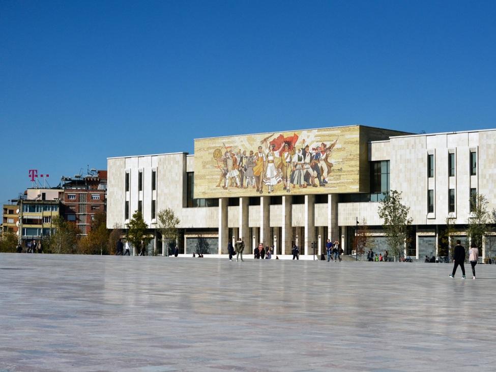 Blick auf einen großen Platz. Im Hintergrund ein Gebäude mit großem, buntem Wandbild.
