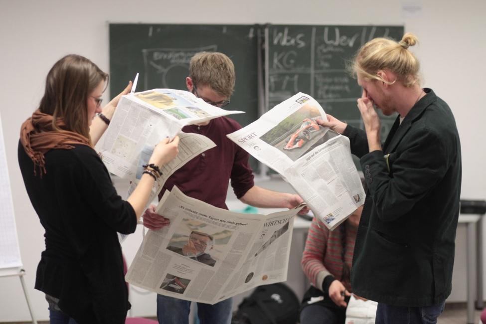 kulturweit-Freiwillige lesen Zeitung in einem Seminarraum.