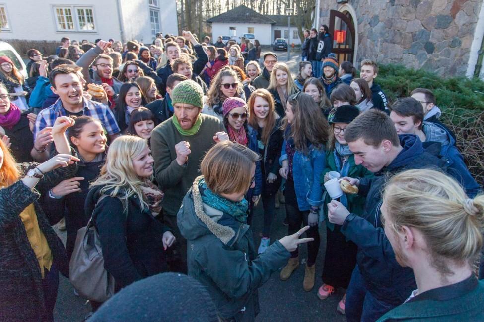 Junge Menschen spielen im Freien Schere-Stein-Papier.