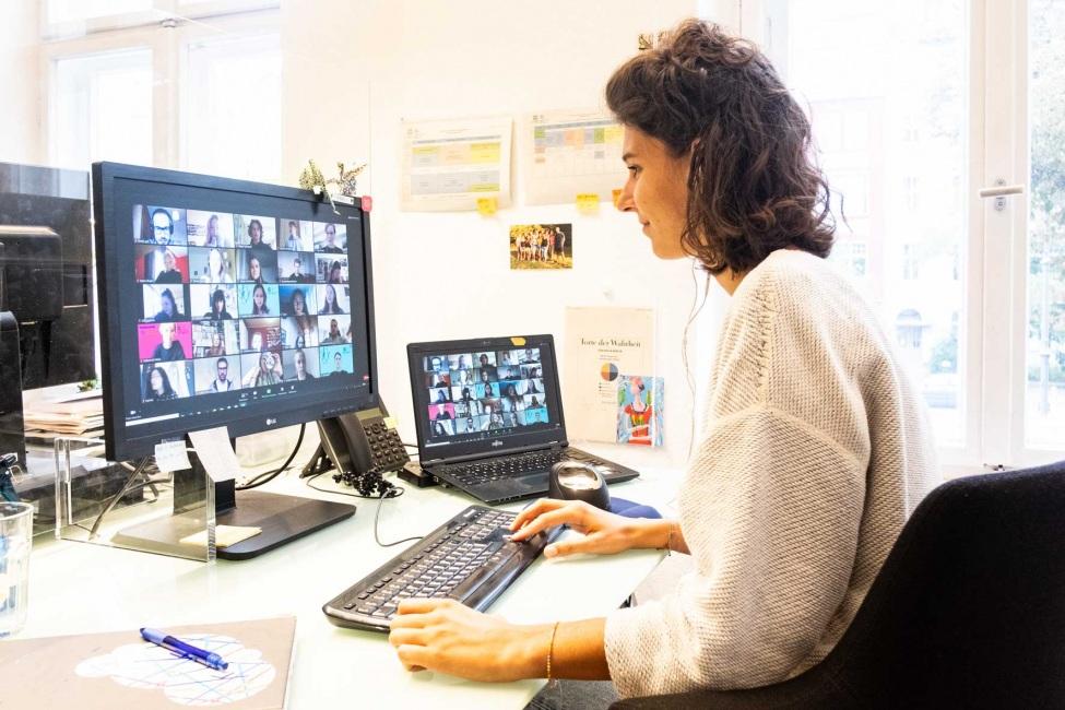 kulturweit-Mitarbeiterin sitzt beim Online-Vorbereitungsseminar vor zwei Bildschirmen, auf denen Menschen an einer Zoom-Konferenz teilnehmen.