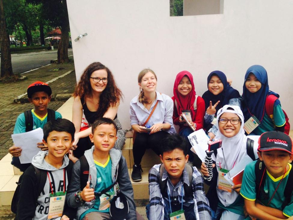 Christin mit Schülern, die Umfragen auf Englisch durchführen für den Unterricht