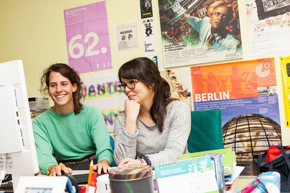 kulturweit-Freiwillige am Goethe-Institut arbeitet mit eine Kollegin am PC.