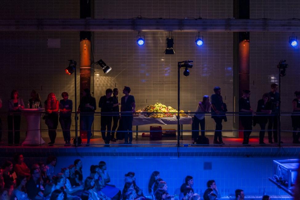 Menschen stehen während einer Feier am Rand eines stillgelegten Schwimmbeckens.