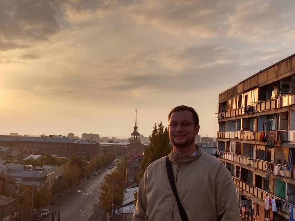 Max vor der Stadtkulisse im Sonnenuntergang. Im Hintergrund Gebäude
