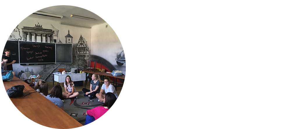 Die Klasse von Marie-Luise Loewe sitzt im Kreis auf dem Boden vor einer Schultafel und diskutiert.