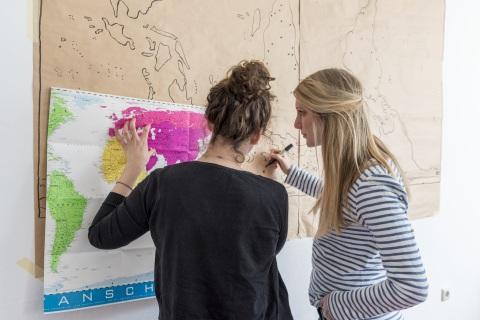 Freiwillige vor einer Weltkarte