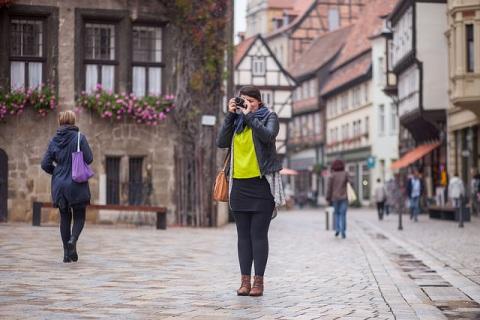 Welterbe-teamerin fotografiert vor historischem Gebäude