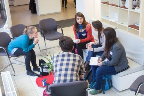Junge Menschen im Gespräch auf einer Messe.