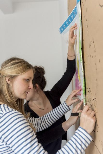 Zweit Frauen stehen an einer Landkarte und zeichnen diese kopfüber.