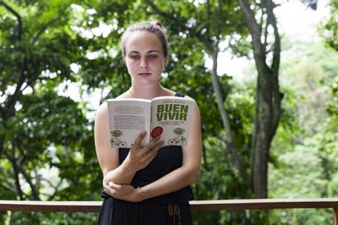Alumna mit Buch zu Buen Vivir.