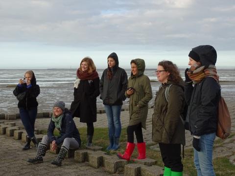 Eine Gruppe von Menschen steht im Wattenmeer.
