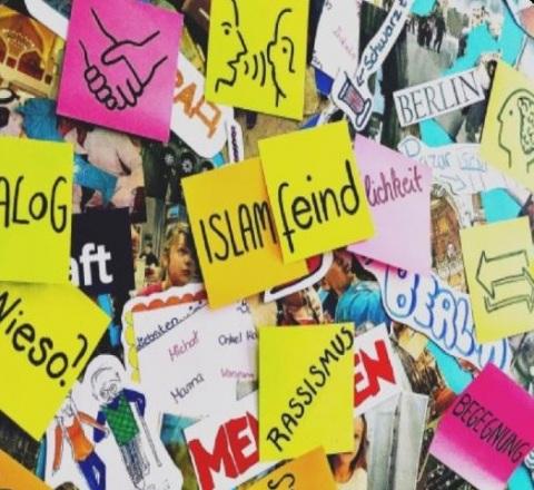 Post-Its auf einer Wand mit verschiedenen Begriffen wie Rassismus, Islamfeind, Dialog.