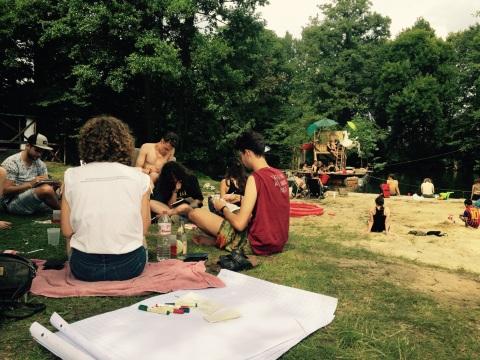 Workshop-Teilnehmende sitzen auf der Wiese und arbeiten.