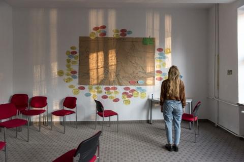 Freiwillige schaut auf eine Weltkarte an der Wand, die mit zahlreichen Zusatzinformationen zu verschiedenen Länden versehen ist.