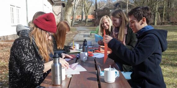 Sechs kulturweit-Freiwillige sitzen an einem Tisch im Freien und falten Briefe.