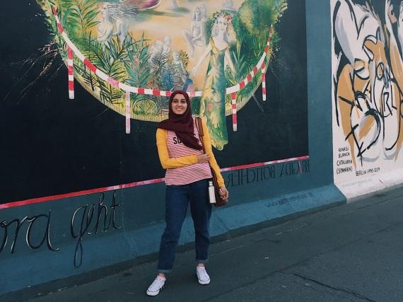 Salma vor einem Stück der alten Berliner Mauer