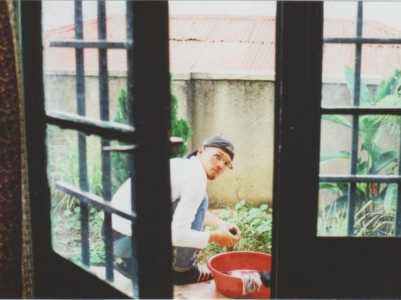 Loe auf der Terasse knieend, aus dem Inneren des Hauses fotografiert