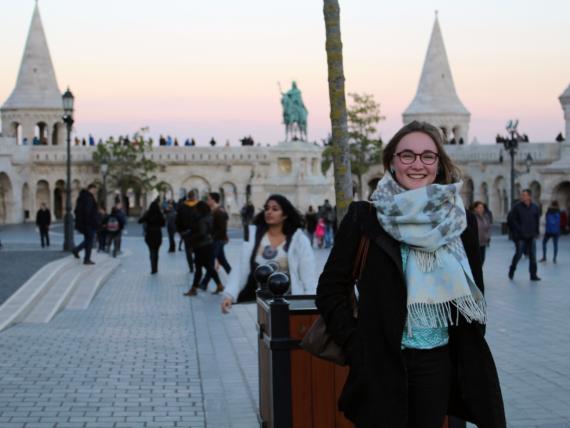 Foto von Kari Lenke auf einem großen Platz, im Hintergrund Menschen und historische Gebäude