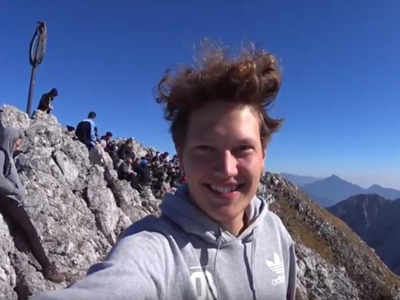 Selfie von Christoph auf dem Berggipfel vor slowenischer Bergkulisse